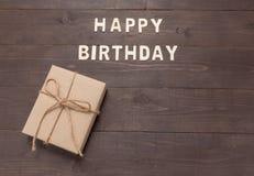 Buon compleanno e contenitore di regalo su fondo di legno con lo spazio della copia Immagini Stock Libere da Diritti