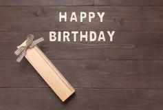 Buon compleanno e contenitore di regalo su fondo di legno con lo spazio della copia Immagine Stock