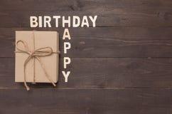 Buon compleanno e contenitore di regalo su fondo di legno con lo spazio della copia Fotografie Stock