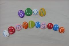 Buon Compleanno, feliz cumpleaños italiano con las piedras coloreadas sobre la arena blanca imagen de archivo libre de regalías