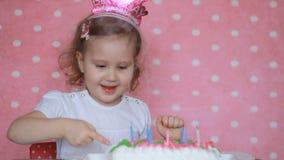 Buon compleanno Il bambino spegne le candele sul dolce al partito e fa un desiderio Bambino divertente della bambina Fondo rosa archivi video