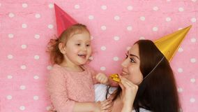 Buon compleanno La donna ed il bambino nella festa ricopre i corni di salto, sorridere e la risata Madre e figlia divertendosi e stock footage