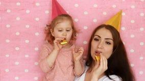 Buon compleanno La madre e la figlia nella festa ricopre i corni di salto, sorridere e la risata Donna e bambino divertendosi e archivi video