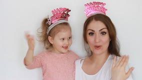Buon compleanno La madre e la figlia sorridono, si divertono, risata ed e cantano una canzone con le congratulazioni Una donna e  archivi video