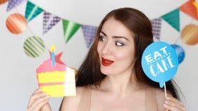 Buon compleanno La ragazza divertente sorride, tiene in mani agglutina e spegne una candela di carta video d archivio
