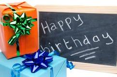 Buon compleanno scritto su una lavagna dell'ardesia con i regali Fotografia Stock