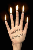 Buon compleanno su una mano con le candele del dito Immagine Stock