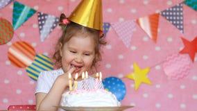 Buon compleanno Una ragazza sveglia del bambino mangia un dolce e lecca il suo dito stock footage