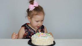 Buon compleanno Una ragazza sveglia del bambino mangia un dolce e lecca il suo dito archivi video