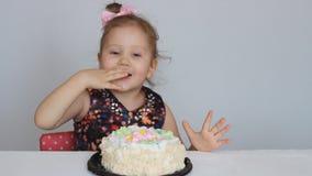 Buon compleanno Una ragazza sveglia del bambino sorride, si rallegra, applaude, mangia un dolce e lecca il suo dito stock footage