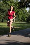 Buon divertimento per pattinare di rullo con le gambe lunghe della ragazza Fotografie Stock