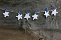 Buon Natale che appende le stelle di legno bianche della decorazione e C blu Fotografie Stock Libere da Diritti