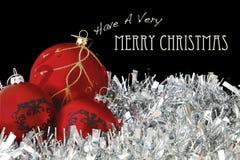 Buon Natale con le bagattelle rosse su lamé Immagini Stock