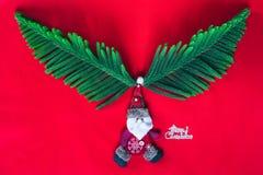 Buon Natale con le foglie del corno di Santa Claus della bambola fotografia stock