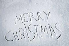Buon Natale dell'iscrizione scritto su neve Immagini Stock