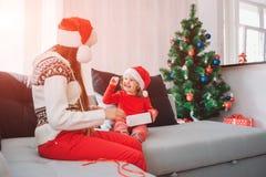 Buon Natale e buon anno Immagine del bambino felice che si siede sul sofà e dolce rotondo bianco della tenuta sul piccolo Esamina fotografie stock