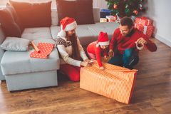 Buon Natale e buon anno Immagine di piccolo assistente che tiene pezzo di carta per il regalo Lei sorriso dei genitori giovane immagini stock
