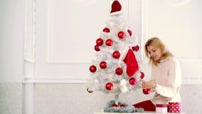 Buon Natale e buon anno La ragazza ha decorato l'albero di Natale, durante in vestito da Natale Ragazza sensuale per stock footage
