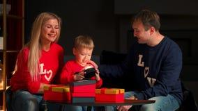 Buon Natale e bambini svegli allegri e genitori di feste felici che aprono i regali Pigiami d'uso del ragazzo divertendosi vicino video d archivio