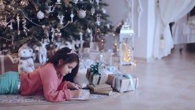 Buon Natale e feste felici! La ragazza sveglia del piccolo bambino scrive la lettera a Santa Claus vicino all'albero di Natale archivi video