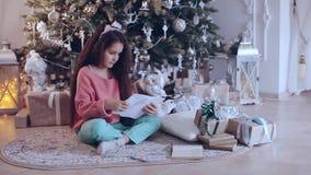 Buon Natale e feste felici! La ragazza sveglia del piccolo bambino scrive la lettera a Santa Claus vicino all'albero di Natale video d archivio