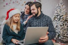Buon Natale e feste felici mamma allegra, papà e la sua ragazza sveglia della figlia per utilizzare un computer portatile Genitor fotografie stock libere da diritti