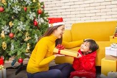 Buon Natale e feste o buon anno felici La mamma dà i regali ai bambini La ragazza sveglia dà a sua madre cara un regalo nuovo fotografia stock libera da diritti