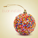 Buon natale, merry christmas in italian. A christmas ball coated with nonpareils of different colors and the sentence buon natale, merry christmas written in Royalty Free Stock Photos