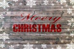 Buon Natale rosso scritto sul bordo di legno con il fiocco di neve Immagine Stock Libera da Diritti