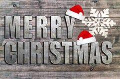 Buon Natale scritto sul bordo di legno con il fiocco di neve ed il cappello di Santa Immagini Stock Libere da Diritti