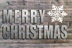 Buon Natale scritto sul bordo di legno con il fiocco di neve Immagini Stock