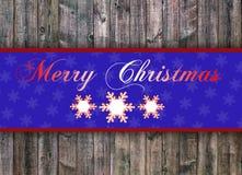 Buon Natale scritto sul bordo di legno con il fiocco di neve Immagine Stock