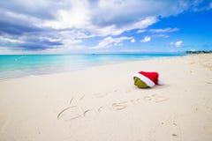 Buon Natale scritto sulla sabbia bianca della spiaggia con Immagini Stock Libere da Diritti