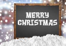 Buon Natale sulla lavagna in bianco con la città e la neve di offuscamento Fotografie Stock