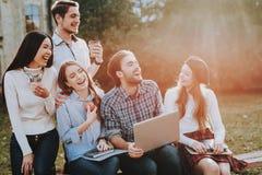 Buon umore Gruppo di giovani Computer portatile siedasi fotografia stock libera da diritti