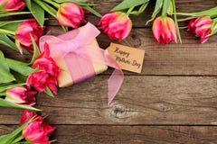 Buona Festa della Mamma regalo ed etichetta con il confine d'angolo dei fiori rosa contro un fondo di legno rustico immagini stock libere da diritti