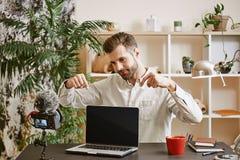 Buona scelta! Blogger bello di tecnologia che indica sul nuovo computer portatile con la macchina fotografica su priorità alta immagini stock