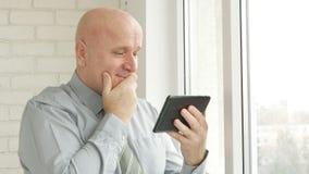 Buone notizie e sorriso di Using Tablet Read dell'uomo d'affari fotografie stock libere da diritti