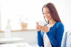 Buongiorno! Chiuda sul ritratto di incantare il caffè bevente della ragazza castana vaga È sonnolenta e rilassata, in blu casuale immagini stock libere da diritti