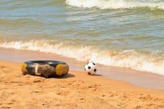 Buoy. Black life buoy and football on beach royalty free stock photo