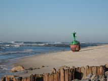 Buoy on the beach. A green and red buoy washed up on an ocean beach near eroded pilings Royalty Free Stock Photos