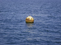 A buoy floating on blue ocean water Stock Photos