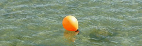 Buoy floating in the clear water Stock Photography