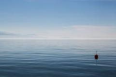 Buoy floats on Lake Geneva. A buoy rhythmically bobs on Lake Geneva Stock Photos