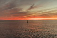 A buoy guards the entrace to a bay within a sunset in Cape Cod, Massachusetts royalty free stock photo