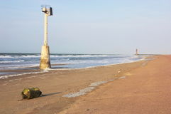 Buoy and lighthouse in distance. A long beach with a buoy, and a lightouse in distance Royalty Free Stock Image
