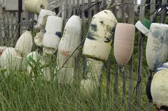 Buoy parking lot. Old bouys hanging from fence in Hamptons stock images