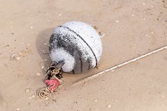 Buoy part of fishing gear thrown on the sandy shore of the ocean old foamy round weathered design royalty free stock images