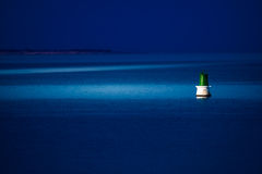 A buoy is reached at night to be repaired. A buoy is reached at night by a patrol boat to be repaired Royalty Free Stock Photography