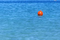 Buoy at right side on blue ocean like emergency sign Stock Photos